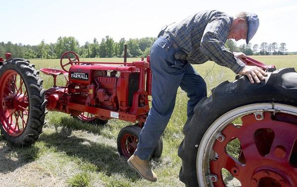 In this 2008 file photo, John Edwards of Smithfield climbs down from one of the vintage tractors in his collection which at the time numbered over a dozen.