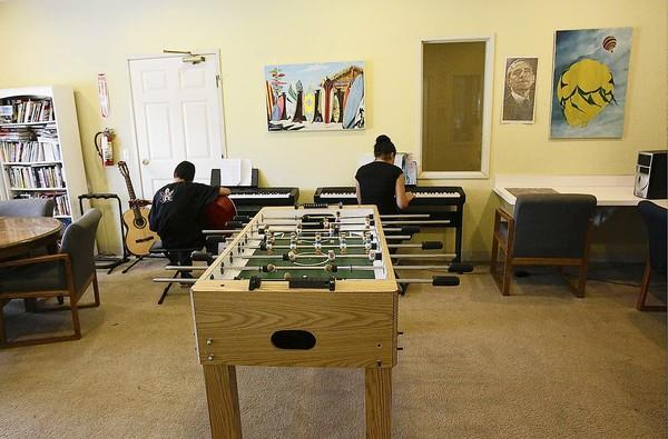 Residents at the Huntington Beach Youth Shelter play instruments in the recreation room on Tuesday.