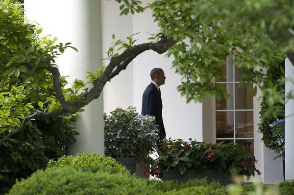 President Obama walks to the Oval Office at the White House in Washington.