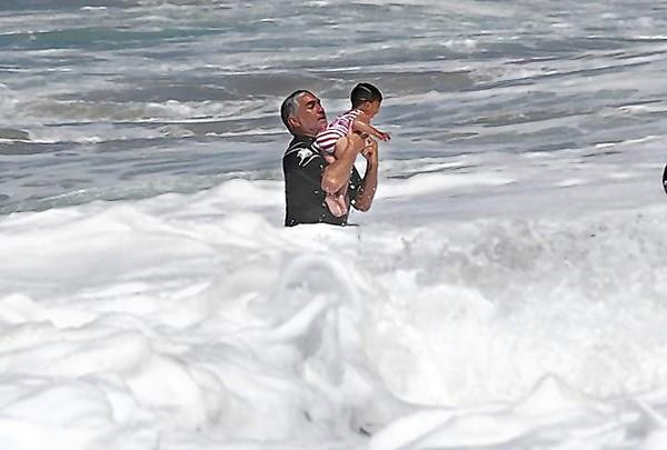 Pat Watson rescues a baby who was knocked from his mother's arms and into the strong shorebreak at Aliso Beach on Monday.