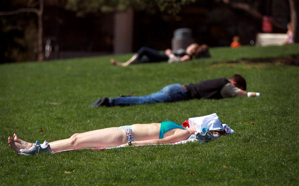 Mary Margaret Dineen, bottom, dons a bathing suit at Scoville Park in Oak Park, Ill., as temperatures rise into the mid-80s on the first day of Spring on Mar. 20, 2012.