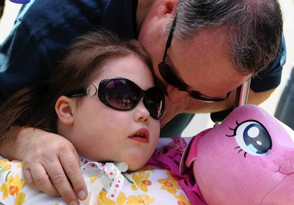 Kira Mammoser, 9, gets a kiss from her dad, Chuck, as she gets a visit from two Chicago police horses on the grounds of Advocate Children's Hospital Park Ridge on May 8.