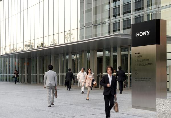 Visitors walk at the entrance of Sony headquarters building in Tokyo on May 9, 2013.