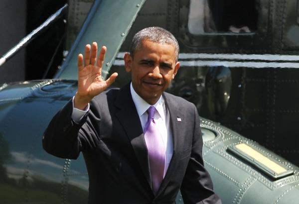 US President Barack Obama waves as he walks across the South Lawn on May 30, 2013 upon return to the White House in Washington, DC.