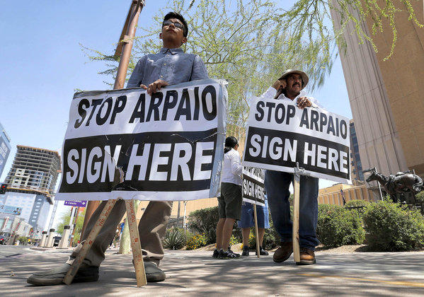 Simon Lopez, left, and Hiliaro Islas try to collect signatures this week in Phoenix in an effort to recall Maricopa County Sheriff Joe Arpaio. The recall effort failed Thursday.