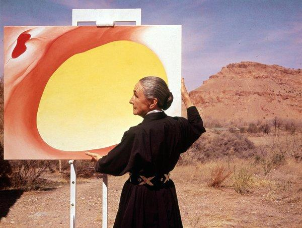 "American artist Georgia O'Keeffe adjusts a canvas from her ""Pelvis Series: Red With Yellow."" A new tour of her home in Abiquiu, N.M., gives visitors unusual access."