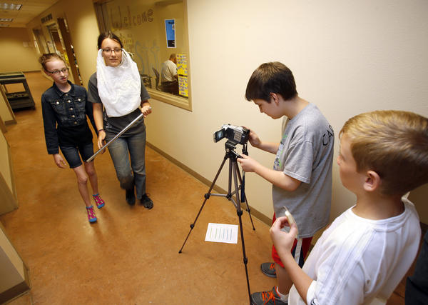 Peyton Johnson, far left, and Christina Grettler act out a scene as Matthew Carpenter, center, videotapes and Gabe Goetz looks on Thursday in a basement hallway of the technology center on the campus of Northern State University. The four students were taking part in an audio and video summer camp sponsored by NSU.
