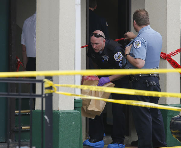 A Chicago police officer removes evidence bags as others investigate the scene of an apparent murder-suicide attempt of a 5-month-old boy who was allegedly stabbed and killed by his mother at the Diplomat Hotel located at 5200 block of North Lincoln Avenue in Chicago.