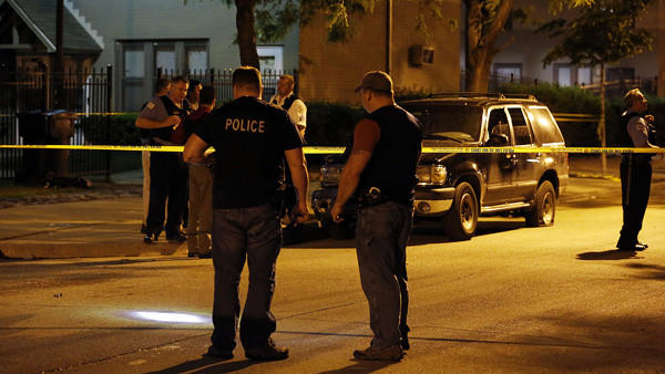 Chicago police officers investigate the shooting of 4 people near the 1200 block of S. Throop late Thursday, May 30, 2013. 3 of the victims are believed to be female. (Stacey Wescott/Chicago Tribune)