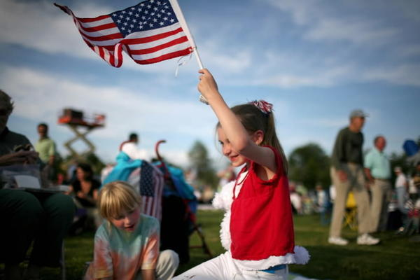 Rachel Bugella (6) of Wethersfield, left, plays while Jillian Amoroso (7) right, also of Wethersfield, holds an American flag as they wait for the start of the Talcott Mountain Music Festival in Simsbury in 2007.