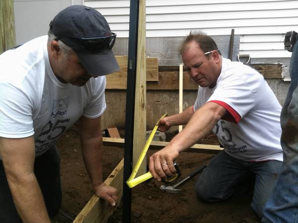 Jeff Buchholz, left, and Jim Sayers of Enfield HomeFront work on installing a ramp at 89-year-old Florence Lynch's Harris Street home in Enfield. HomeFront provides repairs to households of low-income homeowners.