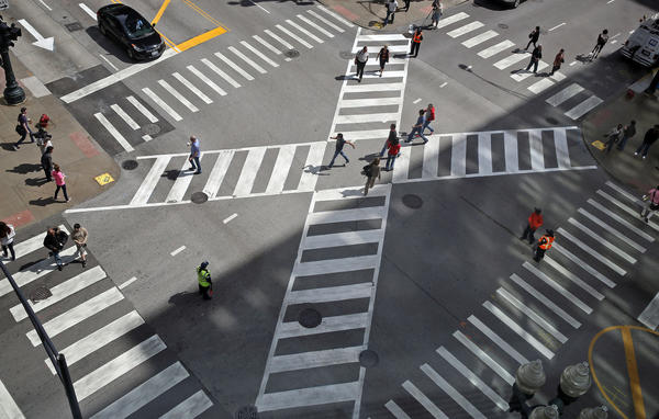 "People cross the intersection of Jackson Boulevard and State Street using the ""pedestrian scramble."""
