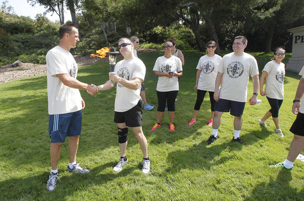 Newport Beach Police Chief Jay Johnson, far left, with Laguna Beach Police Capt. Darin Lenyi as the two departments meet at Newport Coast and Pacific Coast Highway to pass the torch during the Southern California portion of the Law Enforcement Torch Run to benefit the Special Olympics on Thursday.