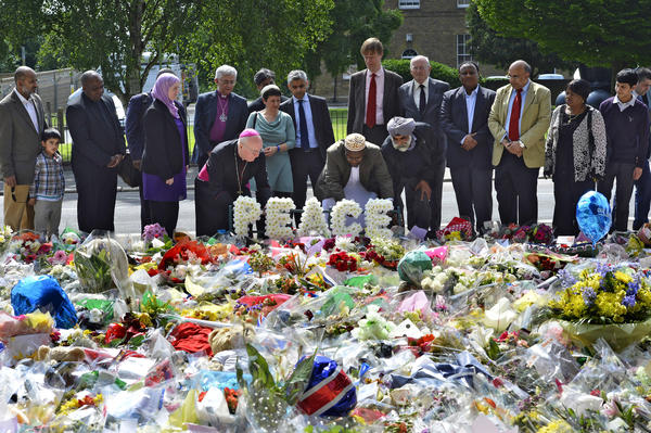 Community representatives and faith leaders lay a floral tribute near the scene of the killing of British soldier Lee Rigby in Woolwich, southeast London. Two men accused of murdering Rigby on a London street last week are in police custody after being discharged from hospital.
