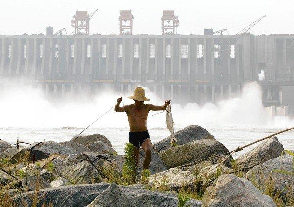 A Chinese man carries a fish he caught below the spillway of the Three Gorges Dam on the Yangtze River, near Yichang, in central China's Hubei province on June 13, 2003.