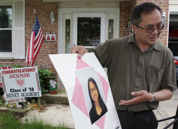 Eric Dizon holds a poster board containing his daughter Jennie outside their Downers Grove home. Jennie was killed by a lighting strike on Thursday.