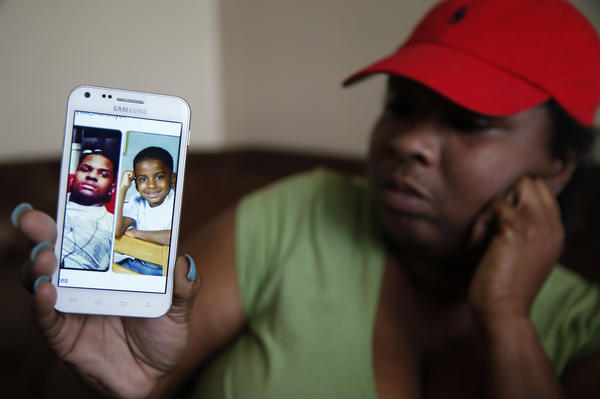 Tominicka Smith, 35, mother of Patrick Sykes, 15, holds a recent image of him and one when he was three, at her Chicago home. Sykes was killed Thursday afternoon.