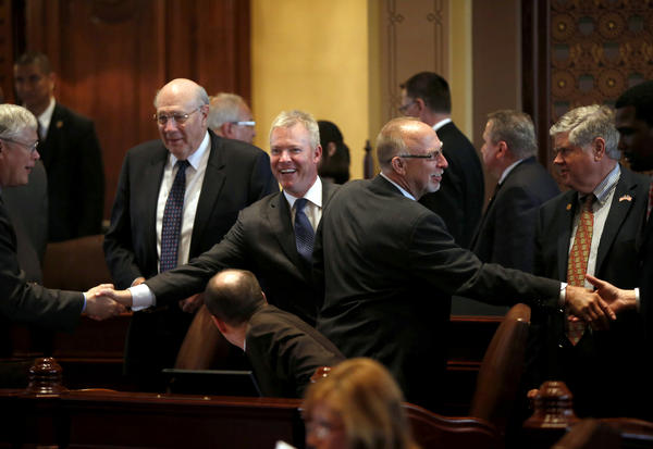 Rep. Brandon Phelps, D-Harrisburg, center left, and Sen. Gary Forby, D-Benton, center right, co-sponsors of the bill, celebrate passage of their concealed carry bill on the Senate floor at the State Capitol in Springfield, Ill.