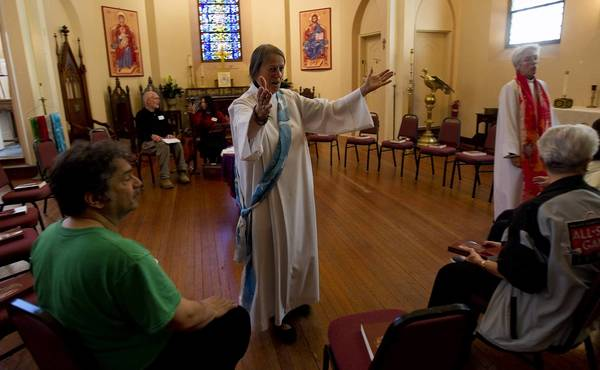 Maria Eitz opens her arms to greet a friend before the Sophia in Trinity congregation's service at Trinity Episcopal Church.