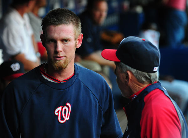 Stephen Strasburg has a discussion with Nationals manager Davey Johnson before being removed from the game after two innings.