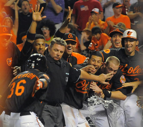 Umpire Greg Gibson backs Orioles teammates away as Chris Dickerson touches home plate after hitting a three-run home run against the Detroit Tigers at Camden Yards.