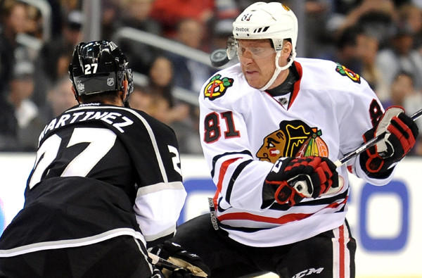 Kings defenseman Alec Martinez and Blackhawks winger Marian Hossa battle for the puck during a regular-season game this season at Staples Center.