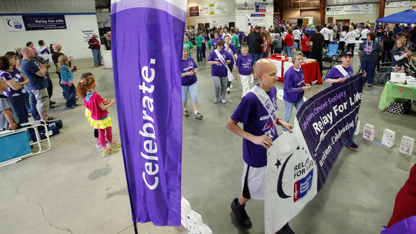 Jayme Skaggs, front center, and Janna Struss, right, both of Aberdeen, carry the Relay for Life banner as they lead the survivor/caregiver lap Friday night to begin the 17th annual Brown County Relay for Life event at the Holum Expo Building on the Brown County Fairgrounds.