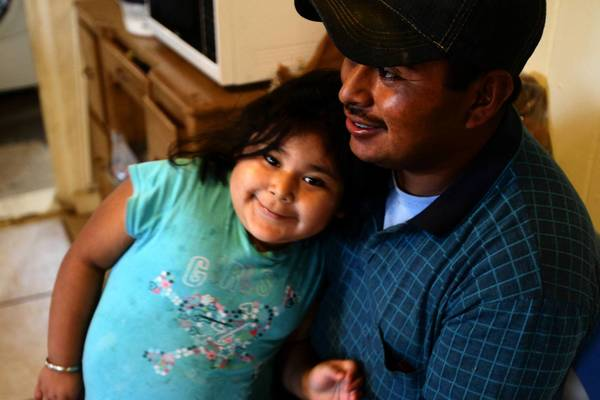 Benito Vasquez greets his 4-year-old daughter, Lydia, after arriving home from another 10-hour workday.