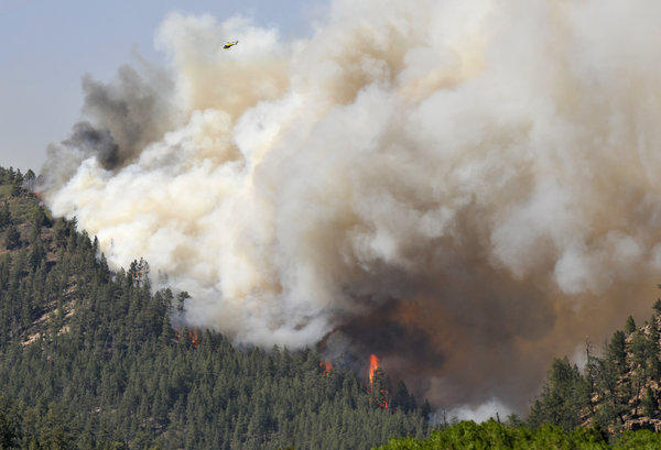 A fast-moving blaze in New Mexico's Santa Fe National Forest prompted evacuations of residences and campgrounds, threatened upscale cabins and vacation homes, and closed a highway.