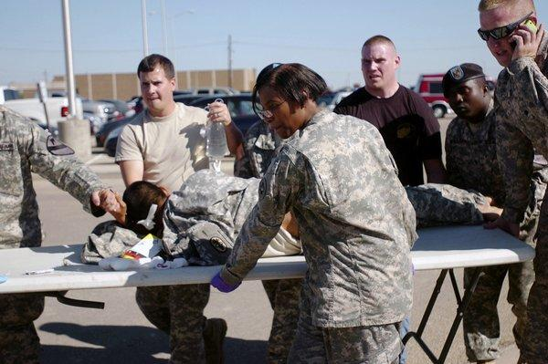 U.S. Army first responders use a table as a stretcher to transport a wounded soldier to a waiting ambulance at Ft. Hood, Texas, on Nov. 5, 2009. Thirteen people died in an attack. The shooting suspect, Major Nadal Malik Hasan, is seeking to represent himself at his court-martial.