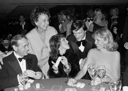 Actress Jean Stapleton, top left, and publisher Hugh Hefner laugh with, from foreground left, Darren McGavin, Ruth Buzzi and Barbara Fisher, during a black-tie casino fundraiser in Los Angeles in 1979.