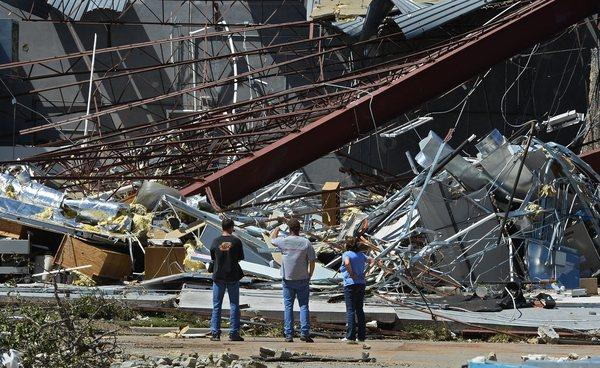 Bystanders look at a crumbled building at a technology school in El Reno, Okla., after a series of tornadoes hit the area. At least nine people were killed and more than 100 injured.