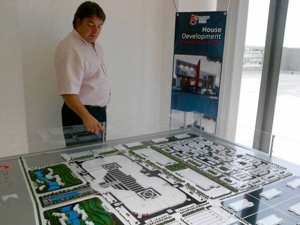 Juan Carlos Lopez, executive director of the Dragon Mart project in Cancun, Mexico, looks at a model of the proposed retail center. Many in Cancun oppose the project.