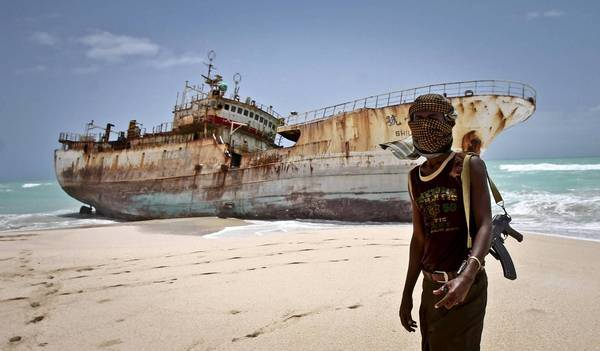 Abdi Ali, a masked Somali pirate, stands near a Taiwanese fishing vessel that washed up in Somalia last year after pirates were paid a ransom and released the crew. There were 35 pirate attacks in the region in 2012, a huge decline from the previous three years.