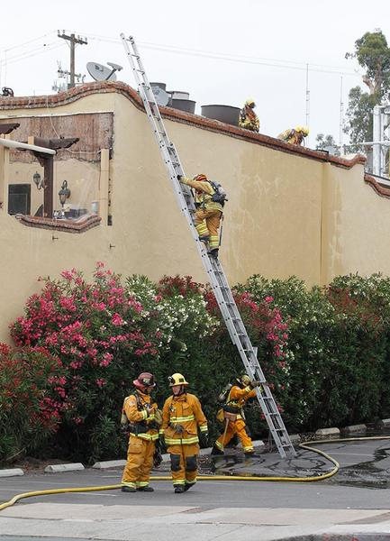Firefighters climb a ladder on the south side of the Mozambique Restaurant. The restaurant was evacuated after a fire started in an upstairs bar area. Firefighters quickly doused the fire and contained it to the upstairs bar and live music area. No injuries were reported.