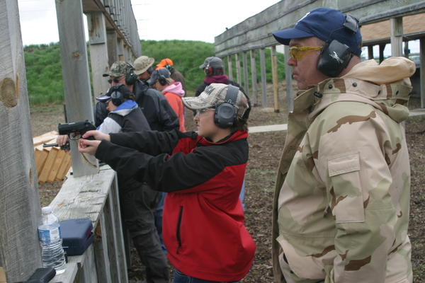 Samantha Bahr of Groton fires her .380-caliber Sig Sauer pistol at the Sportsman's Club of Brown County's rifle range as Brian Kummet looks on at Ladies Day at the range. American News Photo by Scott Feldman