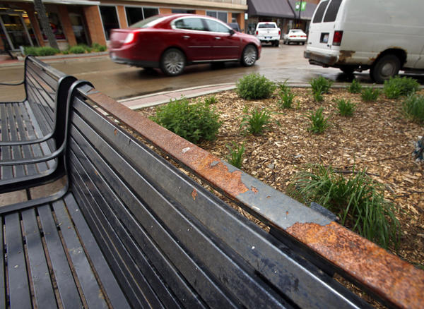 Peeling paint has left a rusty top rail on a bench on the corner of Third and South Main Street in downtown Aberdeen. Some downtown merchants are upset with the fact that benches, fences and other items in the downtown streetscape project are starting to show serious wear after only two years. American News Photo by John Davis