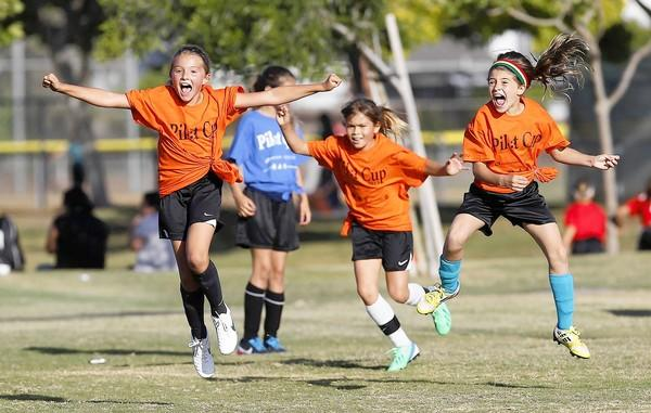 From left, Davis players Karli Rask, Erin Galvin and Sophia Demarco jump for joy after Rask scored during a Daily Pilot Cup girls 3-4 gold division game earlier in the week.