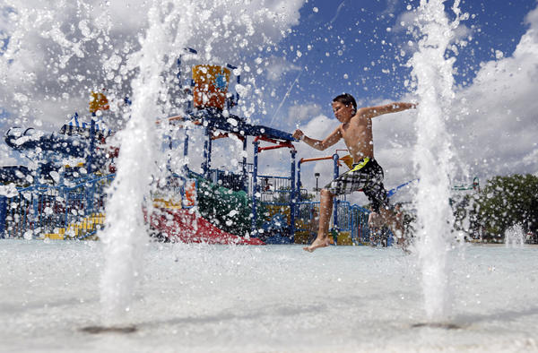 Caiden Frericks, 12, of Aberdeen, high steps past the fountains in the wading pool at the Aberdeen Aquatic Center Thursday. photo by john davis taken 5/30/2013