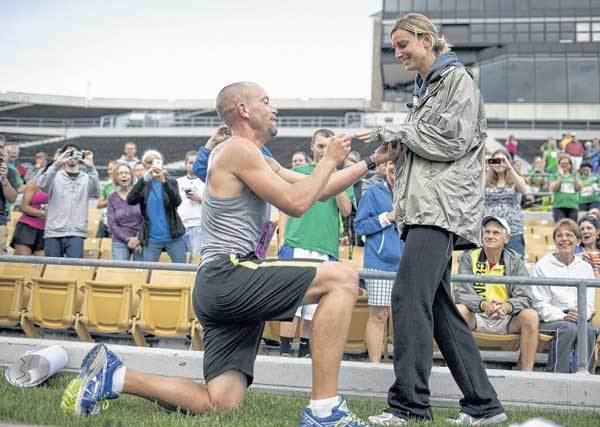 After finishing the Sunburst 10K in 20th place, Tommy Ferry, 35, of Eau Claire, Mich., drops to a knee and slips a ring on the finger of his girlfriend, Shelly Bender, on Saturday at Notre Dame Stadium. Ferry unveiled a sign asking her to marry him as he ran the final 50 yards of the race. She said yes.
