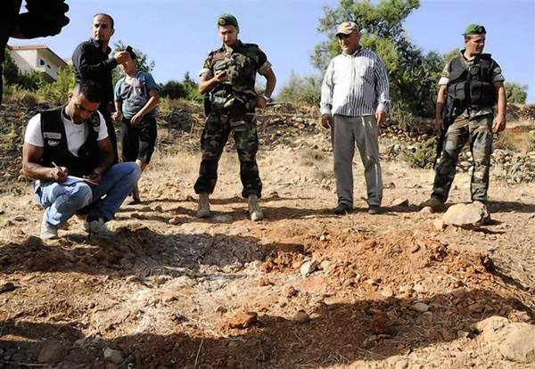 Lebanese soldiers inspect site which was hit by rocket, which residents say was recently fired from Syria overnight, in Seriine.