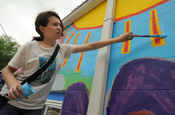Sylvie Lass, 13, helped design the mural with her Hebrew class at Temple Emanuel of Baltimore. Volunteers came to the Baltimore Humane Society Sunday to paint a mural on the front of the Pet Adoption Center to make the plain cinder block building more welcoming. The mural was sponsored by Temple Emanuel of Baltimore, under the supervision of artist Jay Wolf Schlossberg-Cohen.
