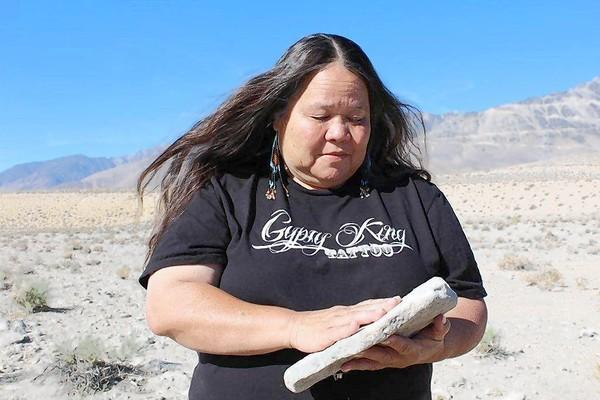 Kathy Jefferson Bancroft, tribal historic preservation officer for the Lone Pine Paiute-Shoshone Reservation, examinines a possible grinding stone she unearthed near a burial site.
