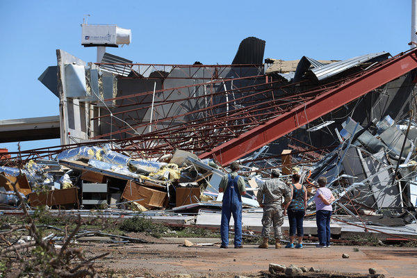People survey the damage at the Canadian Valley Technology Center's El Reno, Okla., campus after it was hit by a tornado.