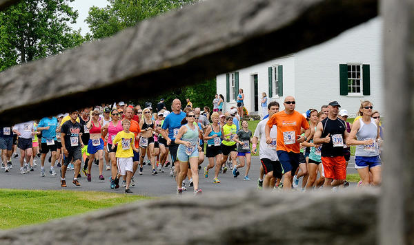 Runners are framed by a wooden rail fence as they pass Dunker Church during the Run Through History 10K at Antietam National Battlefield on Sunday morning.