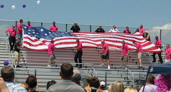 Area firefighters unfurl a flag during the annual Berkeley County (W.Va.) Relay for Life Saturday in Martinsburg, W.Va.