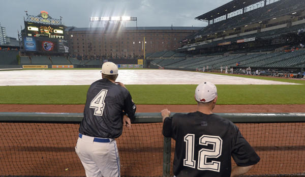 North coaches Dave Warrenfeltz (Williamsport), left, and Ryan Wolfsheimer (Dulaney) watch the rain come down, postposing the Brooks Robinson All-Star baseball game.