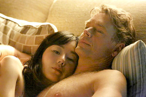 "Yunjin Kim and John Schneider in ""Mistresses."""