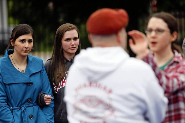 Alexandria Clarke, second from left, holds her friend Sandra Al-Sakkal's arm during a self-defense demonstration by the Guardian Angels Sunday at Schreiber Park.