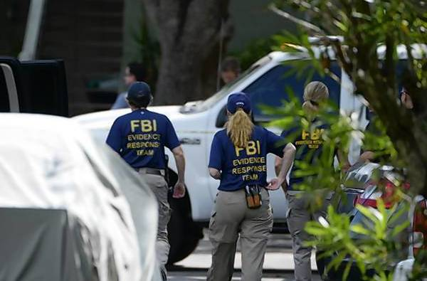 FBI personnel walk through the complex surrounding the apartment, where Ibragim Todashev was shot and killed by FBI agents in Orlando, Florida.